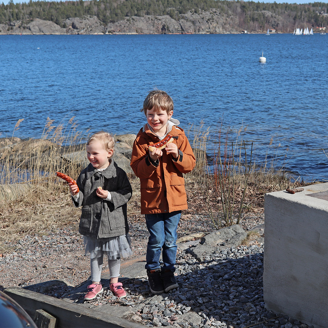 två barn som äter korv och bröd vid strandkanten