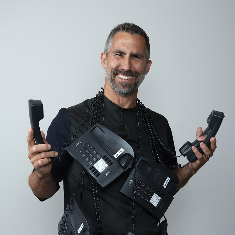 bild på glad manlig receptionist som håller i två telefoner