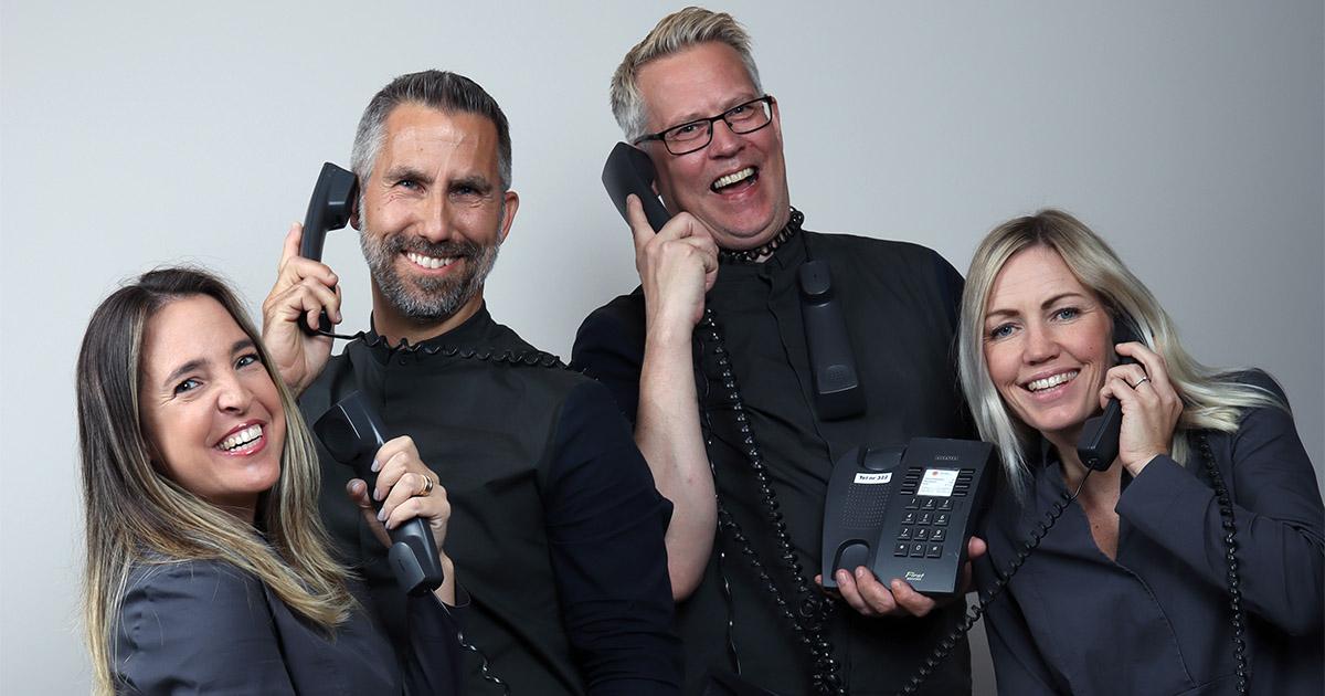 fyra glada receptionister som svarar i telefon