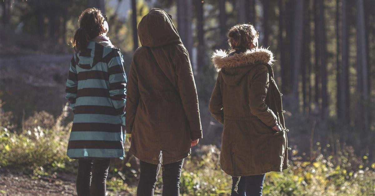 tre kvinnor som promenerar i skogen