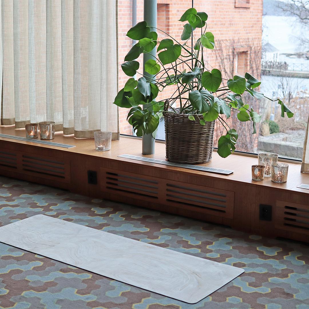 yogamatta på golv vid fönster