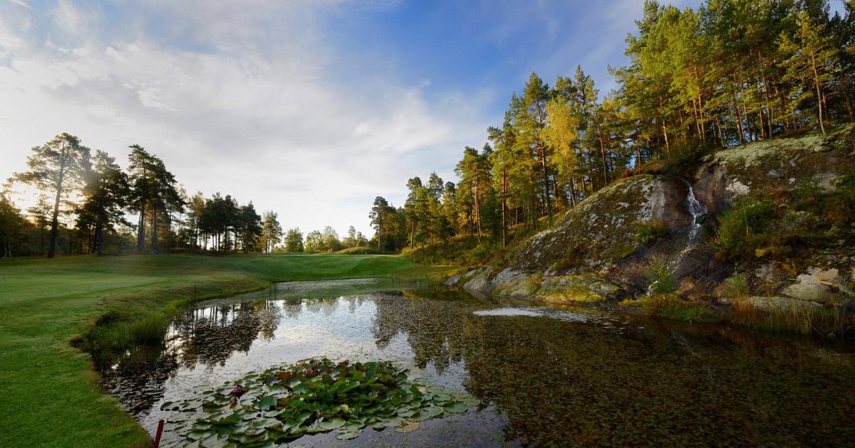 golfbana med sjö och skog