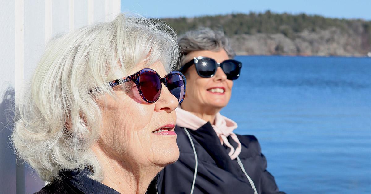 två damer som njuter i solen vid havet