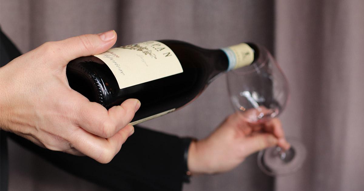 servitris som häller upp rött vin i ett glas