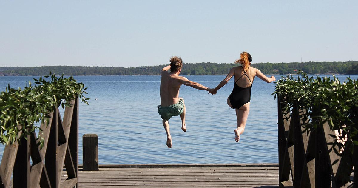 par som hoppar hand i hand från brygga