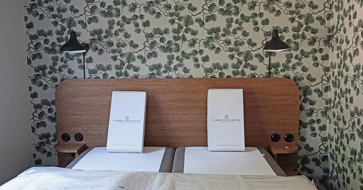 hotellrum med dubbelsäng och mönstrad tapet